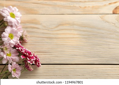 Frame of autumn flowers of chrysanthemums on a natural wooden background. top view