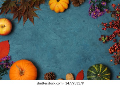 frame of autumnal fruits and vegetables on blue background