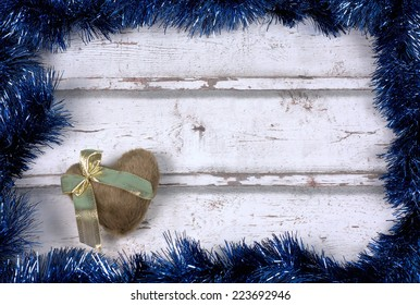 Frame background with blue garlands and a brown heart with golden ribbon against a white wood background.