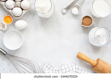 Frame of baking and cooking bread pastry or cake ingredients, flour sugar milk eggs and coconut butter on bright grey background with copy space for text, flat lay