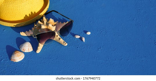 Frame with beach accessories on a nautical theme: yellow straw hat, sunglasses, starfish and shells on a blue background. Vacation concept, sea trip, UV protection, swimming. Copy space. Flatlay