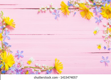 frame of beautiful flowers on pink wooden background