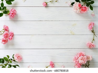 Frame of beautiful pink roses on white wooden background.Top view.Copy space
