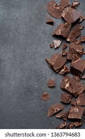Frame or border made of Dark or milk organic chocolate pieces on dark concrete backgound