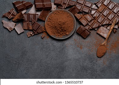 Frame or border made of Dark or milk organic chocolate pieces and cocoa powder on dark concrete backgound