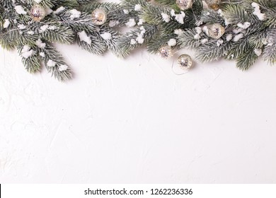 Frame from branches fir tree and fairy lights on  white textured  background. Decorative christmas composition. Selective focus. Place for text. View from above. Flat lay.