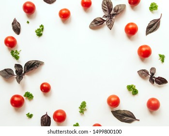 frame of cherry tomato, purple basil leaves and parsley on a white isolated background with space for text