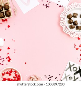 Frame of chocolate candies, heat symbols on pale pink background. Flat lay, top view Valentine's Day or Love concept.