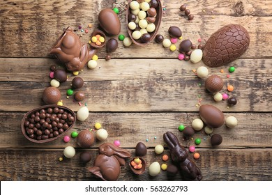 Frame of chocolate Easter eggs, rabbits and sweets on wooden background