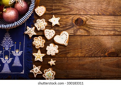 Frame of Christmas accessories and cookies on brown wooden background. Top view