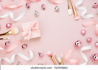 Frame with Christmas ball, gift, ribbon, cosmetic and decorations in pastel pink colour. Holiday Background. Beauty concept. Flat lay, top view