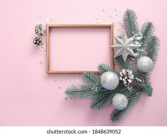 Frame with christmas tree branches and christmas decorations on tender pink background. Top view. Copy space. Christmas sale concept.