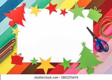 Frame of Christmas trees and decorations made of cardboard and material for making crafts on a background of many colors. Top view. Homemade. Crafts for Christmas. Copy space for text or image.