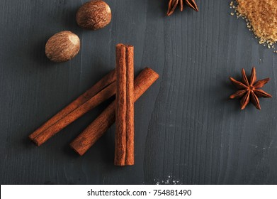In the frame, cinnamon sticks, nutmeg, cane sugar and anise. Spices for cooking homemade cookies. Dark wooden surface. View from above. Close-up.
