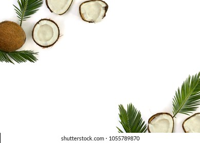 Frame of coconut (Cocos nucifera) with halfs and palm leaves on a white background with space for text. Top view, flat lay.