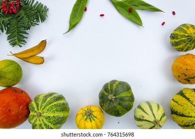 frame from colorful decorative pumpkins ,dry leaves and berries, on a wooden table. Autumn mockup flat lay design
