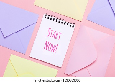 Frame from colorful envelopes and notepad on pink table top view. Worns Start Now. Mockup for business mail, blogging and office correspondence, motivation picture. Flat lay.