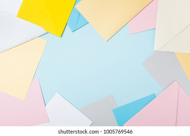 Frame from colorful envelopes on blue table top view. Mockup for business mail, blogging and office correspondence. Flat lay.