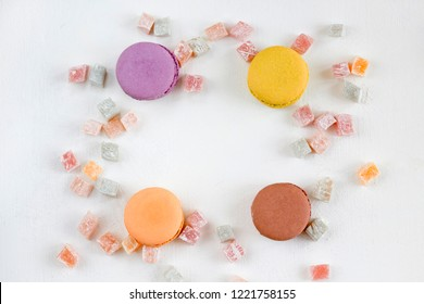 Frame from colorful french macarons and lokum on white background, toned. Confectionery, recipe, menu concept. Top view, flat lay, copy space, layout design.