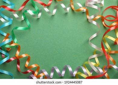 Frame of colorful serpentine streamers on green background, flat lay. Space for text