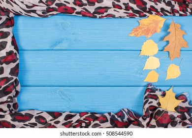 Frame of colorful shawl for woman and autumnal leaves on boards, warm clothing for autumn or winter, copy space for text