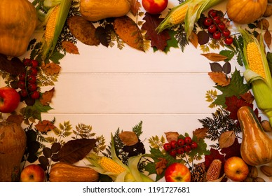 Frame composition with autumn leaves, red apples, corn, walnuts and pumpkins on a old wooden background. Fall texture. Nature september and october background. Copy space, top view. Toned photo.
