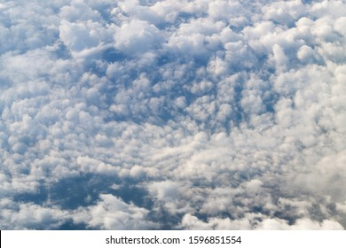 Frame of cumulus clouds swirling in center into a funnel, with blue sky peeking through gaps, aerial photograph taken at altitude of ten thousand kilometers from airplane. Natural abstract background
