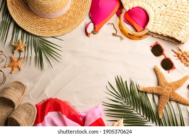 Frame of different beach accessories on sand, flat lay. Space for text