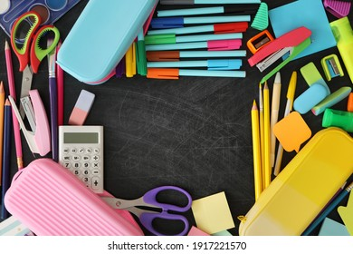 Frame of different stationery on blackboard, flat lay with space for text. Back to school