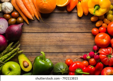 Frame of different types of fruits and vegetables on a wooden table with negative space to place logo or text.