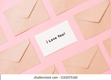 Frame from envelopes and postcard on pink table top view. Words I LOVE You. Valentine concept. Flat lay.