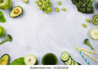 Frame flatlay arrangement with various green fruits and vegetables: lettuce, cucumber, avocado, broccoli, grapes, apples etc and green juice in a glass on cement background. Healthy lifestyle concept