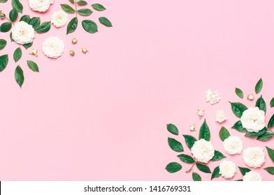 Blütenrahmen Weiße frische Rosen und grüne Blätter auf sanftem rosafarbenem Hintergrund. Flachlage, Draufsicht, Kopienraum. Blumenkarte, Gruß, Urlaubsmuster. Valentinstag Hintergrund Frauentag