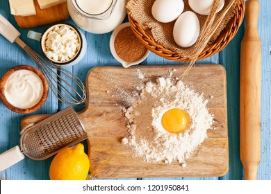 Frame of food ingredients for baking on a blue woodenl background. Cooking flat lay with copy space