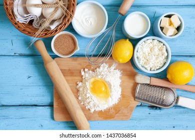 Frame of food ingredients for baking on a blue wooden background. Cooking flat lay for pastry on rustic wood, culinary classes or recipe concept