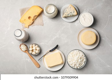 Frame of fresh dairy products on gray background, top view