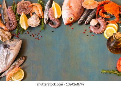 Frame of fresh fish variety and spice on blue wooden background with copy space.