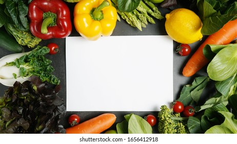 Frame of fresh organic vegetables background and white blank paper on table, Healthy food concept top view.