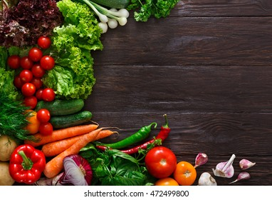 Frame of fresh organic vegetables on wood background. Healthy natural food on rustic wooden table with copy space. Tomato, lettuce, carrot, garlic, zucchini and other cooking ingredients top view