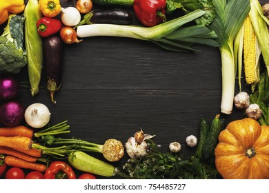 Frame of fresh organic vegetables on wood background with copy space. Healthy natural food on rustic wooden table. Pumpkin, corn, carrot, garlic and other cooking ingredients top view