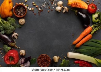 Frame of fresh organic vegetables on wood background. Healthy natural food on rustic wooden table with copy space. Beans and sea satl, carrot, pepper, broccoli and other cooking ingredients top view