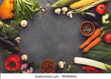Frame of fresh organic vegetables on gray background. Healthy natural food on rustic wooden table with copy space. Beans and sea satl, carrot, pepper, broccoli and other cooking ingredients top view