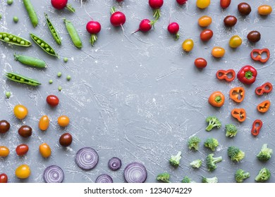 Frame of fresh organic vegetables. Radish, green peas, broccoli, tomato and onion on grey background, with copy space