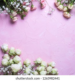 Frame from fresh white gypsofila and white rose flowers on  pink textured background. Top view. Place for text. Square image.