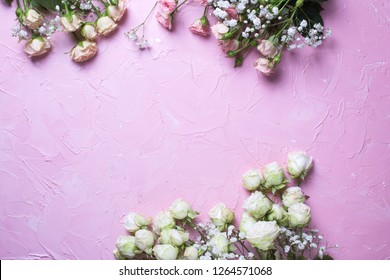 Frame from fresh white gypsofila and white rose flowers on  pink textured background. Top view. Place for text.