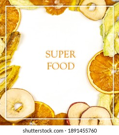 Frame of fruit chips. Healthy and fashionable snack. Trendy eats. Dried slices of orange, apple, pineapple, peach and banana with space for writing. Card with super food. Top view, copy space
