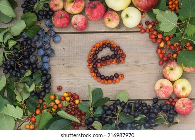 "Frame of fruits and berries with ""E"" letter on a wooden background"