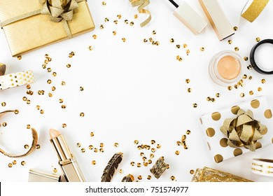 Frame with gift, sequins, makeup cosmetics kit  and other accessories on white background. Composition in gold colors. Flat lay, top view.