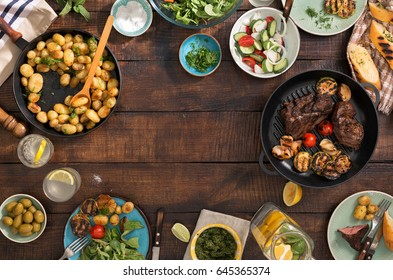 Frame of grilled steak, grilled vegetables, potatoes, salad, different snacks and homemade lemonade, top view. Concept dinner table