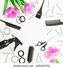 Frame with hairdresser tools - spray, scissors, combs, barrette and tulips flowers on white background. Beauty concept. Flat lay, top view